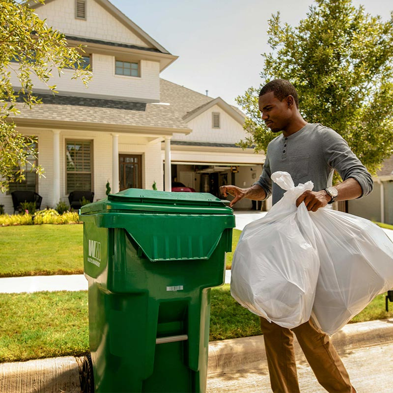 Man putting bags of trash into green WM trash container